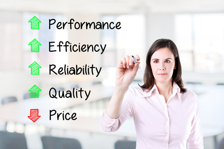 decreased: Businesswoman writing Decreased price compare with Increased Quality, Reliability, efficiency, performance. Office background. Stock Photo
