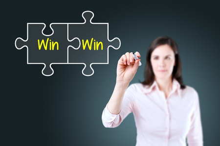 Businesswoman drawing a Win Win Puzzle Concept on the virtual screen. Blue background. Standard-Bild