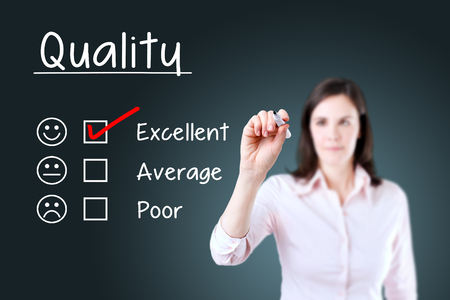 Hand putting the check mark with red marker on excellent quality evaluation form. Blue background.