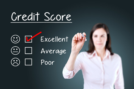 business credit application: Hand putting the check mark with red marker on excellent credit score evaluation form. Blue background.