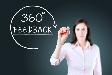 Businesswoman drawing a 360 degrees Feedback concept on the virtual screen. Blue background. Banque d'images
