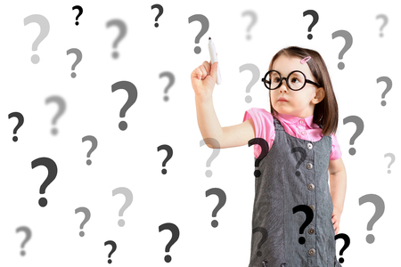 perplex: Cute little girl wearing business dress and writing question mark. White background.
