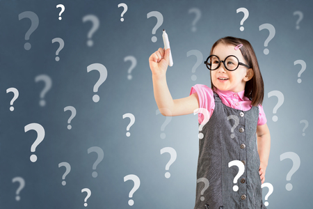 bewilder: Cute little girl wearing business dress and writing question mark. Blue background.