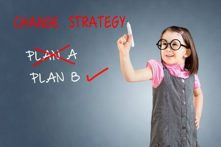 Cute little girl wearing business dress and drawing business plan strategy changing. Blue background.