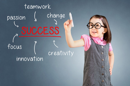 board marker: Cute little girl wearing dress and writing business success diagram on glass board with marker. Blue background. Stock Photo