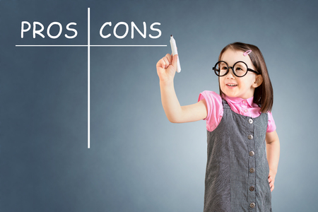 pros: Cute little girl wearing business dress and writing pros and cons comparison concept. Blue background. Stock Photo