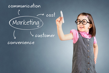 Cute little girl wearing business dress and writing marketing concept - customer, cost, convenience, communication. Blue background.