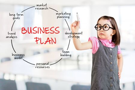 Cute little girl wearing dress business concept and business plan drawing. Office background.