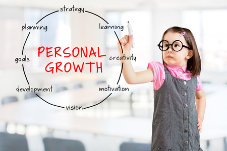 Cute little girl wearing business dress and drawing circular structure diagram of personal growth concept. Office background.