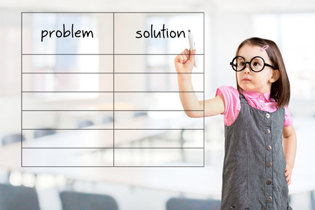 correlate: Cute little girl wearing dress and writing business problem and solution in blank list. Office background.