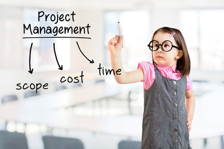 Cute little girl wearing business dress and writing project management concept. Office background.