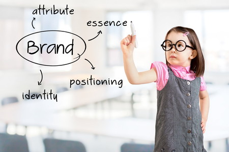 Cute little girl wearing business dress and writing brand concept. Office background. Standard-Bild
