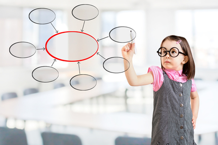 conjoin: Cute little girl wearing business dress and writing diagram of centralization. Office background. Stock Photo