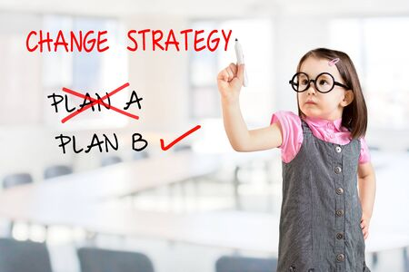 adapting: Cute little girl wearing business dress and drawing business plan strategy changing. Office background. Stock Photo