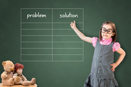 correlate: Cute little girl wearing dress and showing business problem and solution listed in blank on green chalk board. Stock Photo