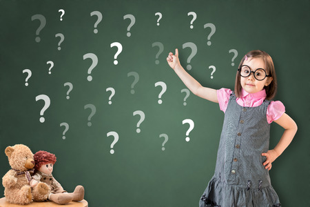 perplex: Cute little girl wearing business dress and showing question mark on green chalk board.