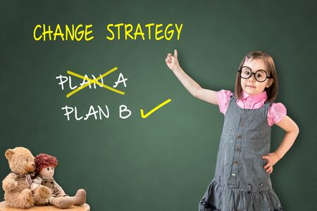 adapting: Cute little girl wearing business dress and showing business plan strategy changing on green chalk board. Stock Photo