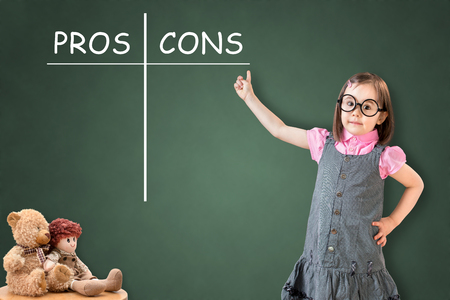 information analysis: Cute little girl wearing business dress and showing pros and cons comparison concept on green chalk board.