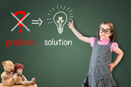 eliminate: Cute little girl wearing business dress and Eliminate problem and find solution on green chalk board.