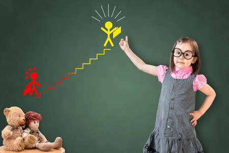 career ladder: Cute little girl wearing business dress and showing the career ladder concept on green chalk board.