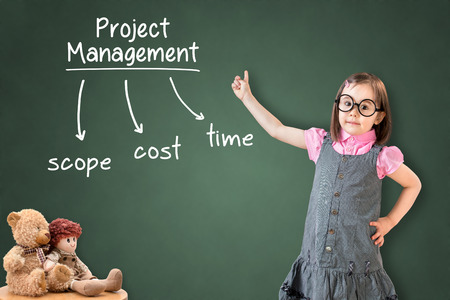 constrain: Cute little girl wearing business dress and writing project management concept on green chalk board. Stock Photo