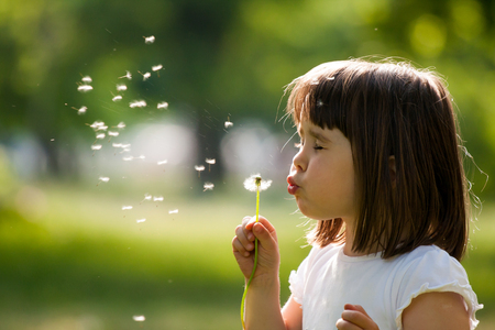 person outdoors: Beautiful child with dandelion flower in spring park. Happy kid having fun outdoors.