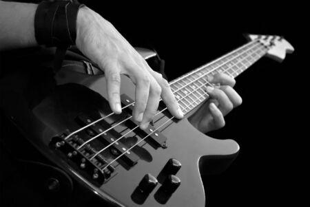 Elektrische bas-gitaar in mannelijke handen, zwart-wit