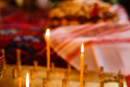 christian halloween: Single candle with dripping wax and blurring lights of many candles in two candlesticks at background. Stock Photo