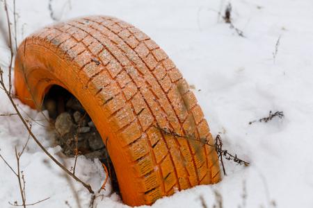 Tyre in the snow Orange tire in the snow