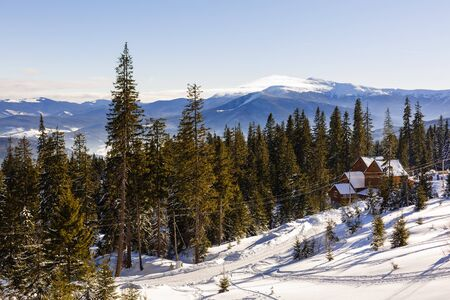 winter mountains landscape with a snowy forest and a wooden hut on a sunny morning