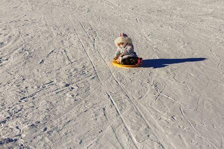 Little girl sliding downhill on tube Child on a sled