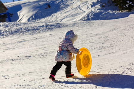 Small girl in winter clothing pushes a wooden sledge through to the top of a snow covered hill. Seen from a low perspective.
