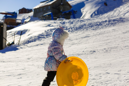 wintersport: Small girl in winter clothing pushes a wooden sledge through to the top of a snow covered hill. Seen from a low perspective.