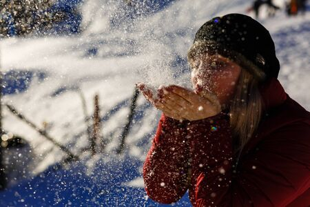 young girl blowing magic snow blows snow from palm