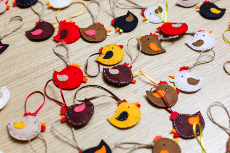 Handmade felt owl toy, felt sheets, scissors, thread, pins, needle on a brown wooden background