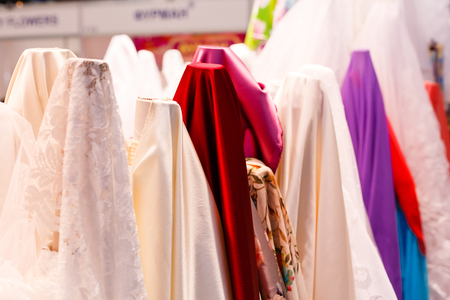 sold small: Wedding dresses hanging on a hanger. Fashion look. Interior of bridal salon.