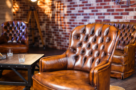 stool: Leather armchair against stone wall. Vintage armchair in loft. Stock Photo