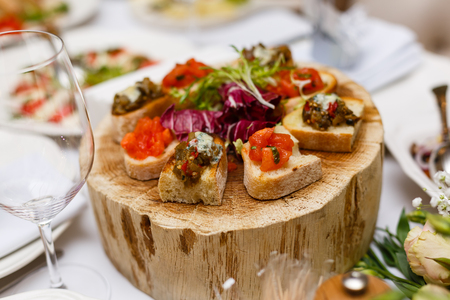 Wooden dish with snacks stands on box on dinner table