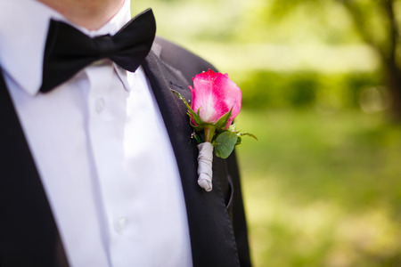 man in a suit corrects hand of a red rose boutonniere Stock Photo