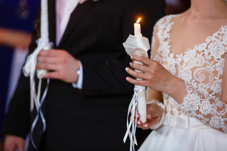 engage: Newlyweds hold burning candles with pastel flowers during ceremony in church Stock Photo
