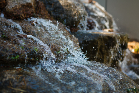 Close up of water splashing on rocks from a waterfall Water on decorative stones
