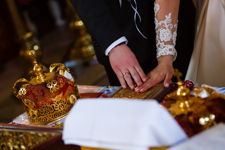 engage: Newlyweds hold their hands on the golden Bible while standing on the knees Stock Photo