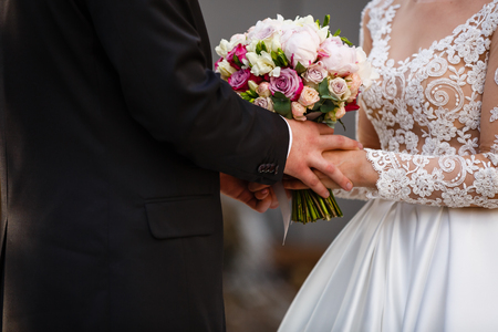 floristics: The bride and groom exchange rings during a wedding ceremony, a wedding in the summer garden