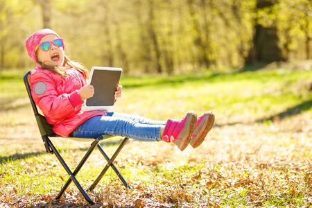 Girl sitting on chair holding tablet