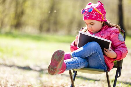 Girl sitting in garden on chair holding tablet
