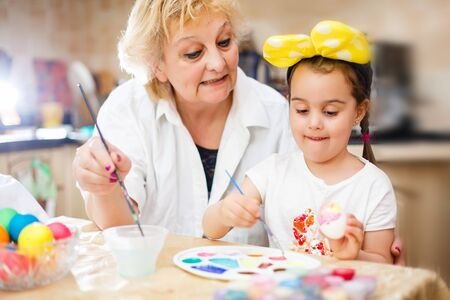 Grandmother with granddaughter are coloring eggs for Easter. white, t-shirt, brushes