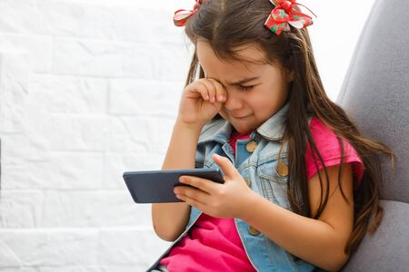 Little girl crying and holding smartphone.The little girl hid her face and cried, holding a mobile phone in her hands. Standard-Bild
