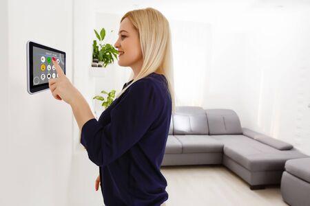 Smart house. Nice joyful woman looking at the sensory panel while pressing it Stock Photo