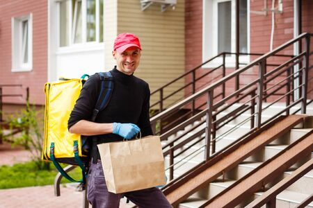 delivery, mail and people concept - happy man delivering food in disposable paper bag to customer home