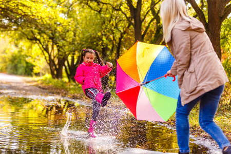 Very cute little girl in pink Jacket and rubber boots is jumping over a puddle on a rainy day